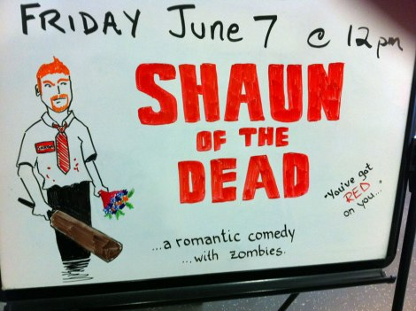 A whiteboard announces Shaun of the Dead will be playing in Lyons on June 7 at 12pm. There is a sketch of the main character, Shaun, next to the title of the movie.